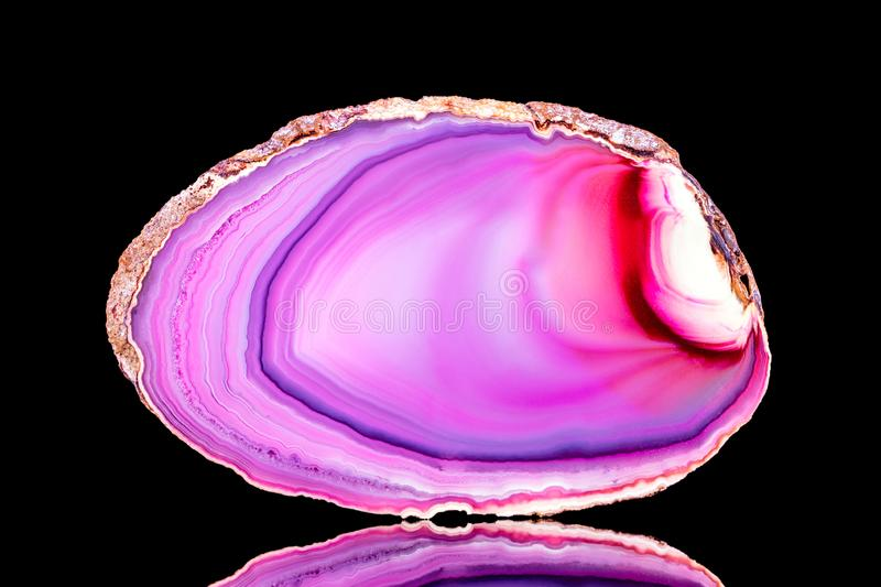 Pink agate slice mineral in front of black background. Mineralogy and esotericism royalty free stock images