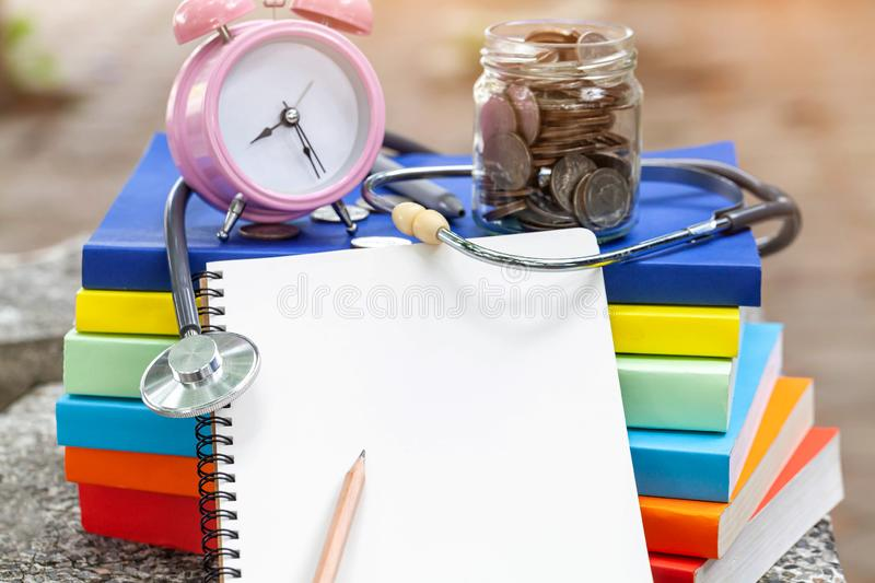 Pink alarm clock closeup standing on pile of books. Business. Or education concept royalty free stock image