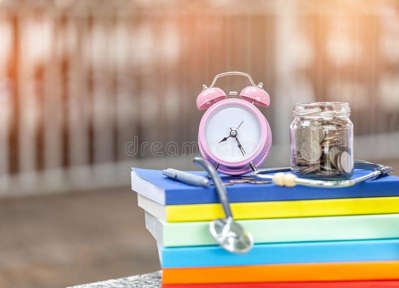 Pink alarm clock closeup standing on pile of books. Business. Or education concept stock photos