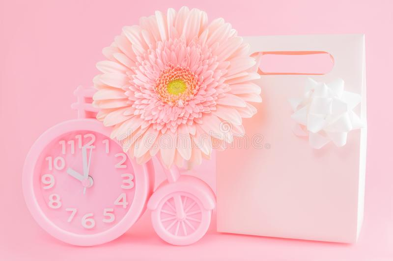 Pink alarm clock, gift box and gerbera flower on pink background. Good morning concept or time for presents stock image