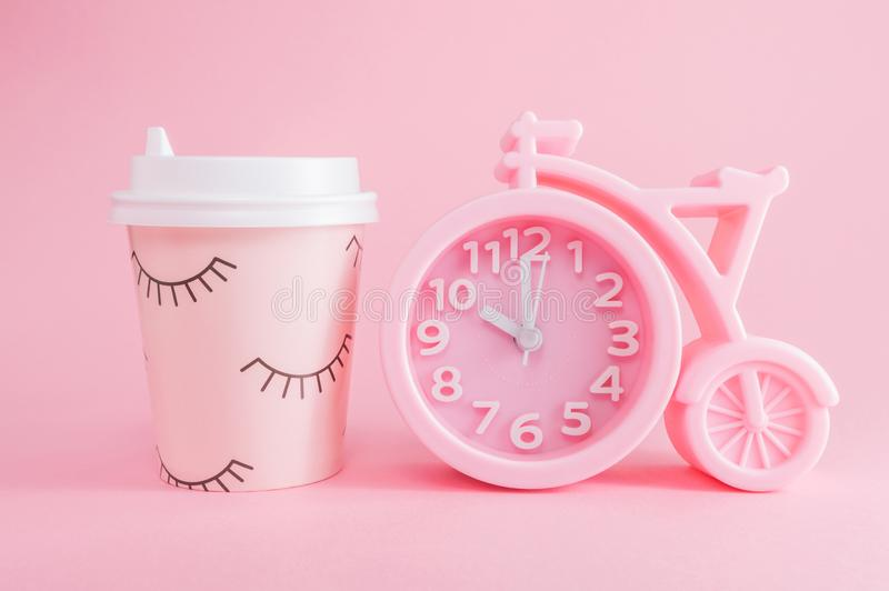 Pink alarm clock and a glass of coffee take-away on a pink background. Coffee time or good morning. Pink alarm clock in the shape of a bicycle and a glass of royalty free stock photo