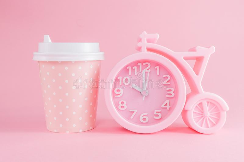 Pink alarm clock and a glass of coffee take-away on a pink background. Coffee time or good morning. Pink alarm clock in the shape of a bicycle and a glass of royalty free stock image