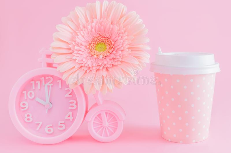 Pink alarm clock, glass of coffee take-away and gerbera flower on pink background. Good morning or coffee time concept. Postcard. Pink alarm clock in the shape royalty free stock photo