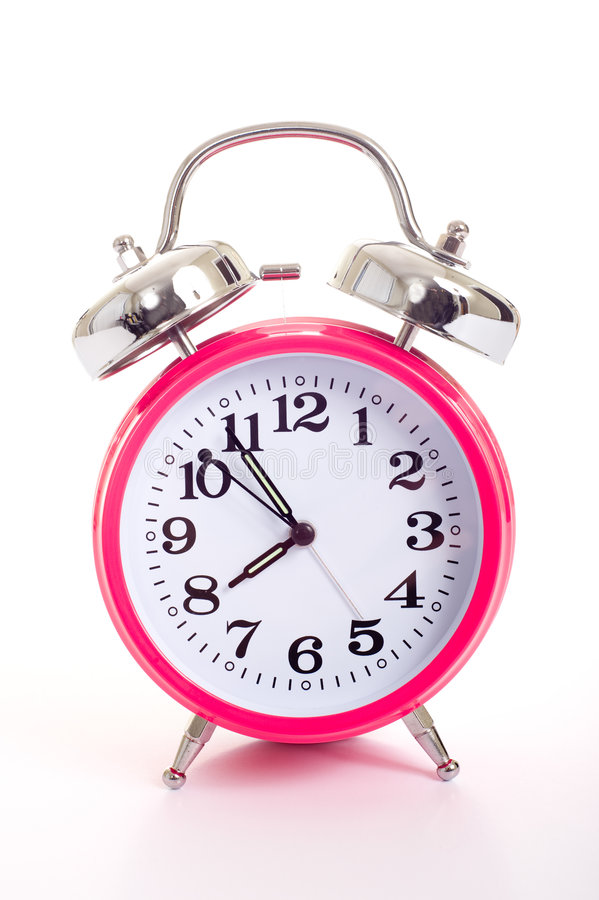A pink alarm clock on a white background. A bright pink vintage looking alarm clock on a white background royalty free stock photo