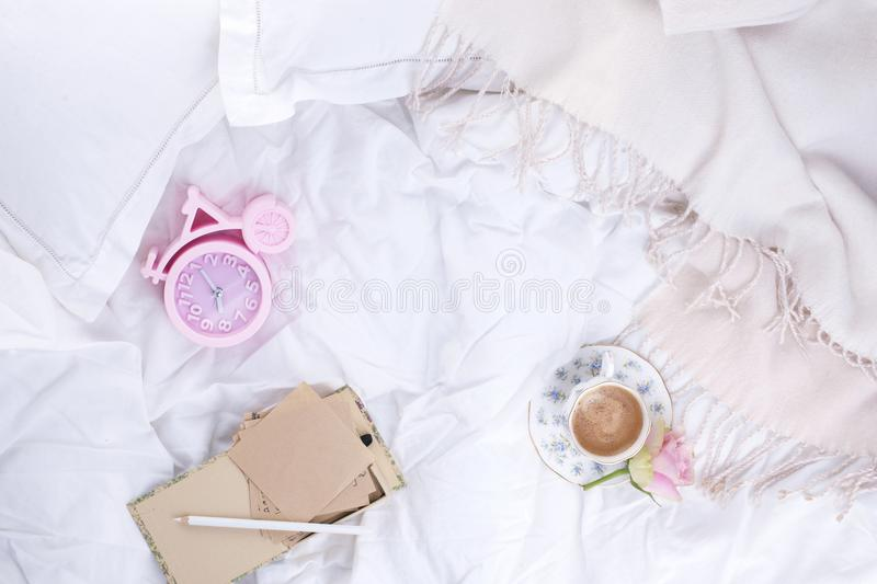 Pink alarm clock, white bed, fragrant coffee and pink roses. Good morning Vintage photo. Copy space. Flat lay stock photos