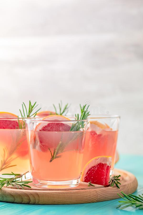 Pink alcoholic cocktail with grapefruit, ice and mint. Fresh pink alcoholic cocktail with grapefruit, ice and mint, drink glasses and ingredients on a blue stock photos