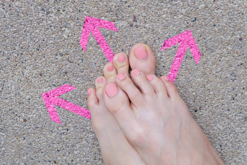 Pink Arrow Choice Concept. Female Bare Feet with Pink Nail Polish Manicure Standing and Many Direction Arrows Choices on the Road stock images