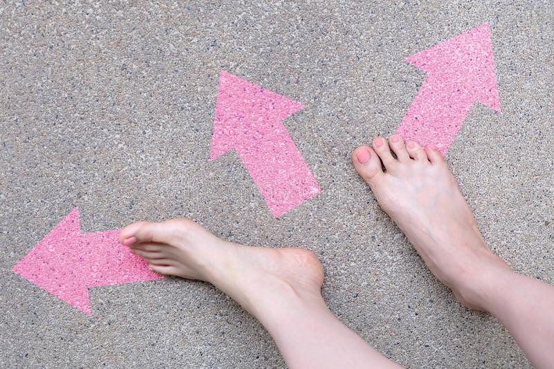 Pink Arrow Choice Concept. Female Bare Feet with Pink Nail Polish Manicure Standing and Many Direction Arrows Choices on the Road stock photography