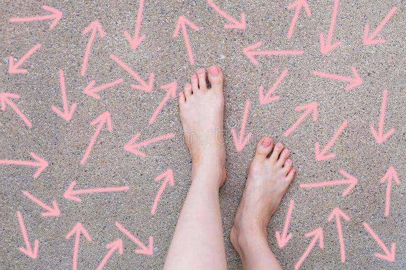 Pink Arrow Choice Concept. Female Bare Feet with Pink Nail Polish Manicure Standing and Many Direction Arrows Choices on the Road royalty free stock photo