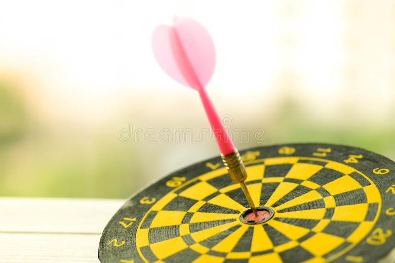 The pink arrow hit on the center of the yellow dart use as meet the target , achieve goal and successful concept stock photography