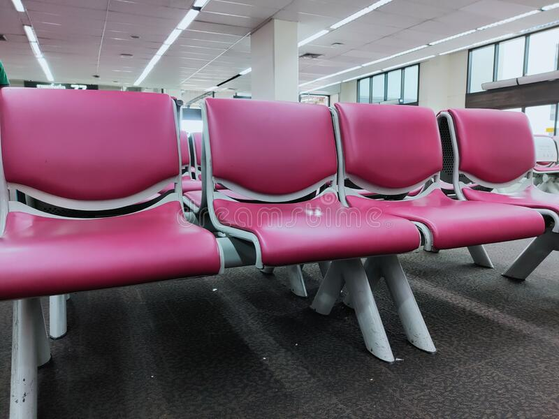 Pink artificial leather chairs lined up waiting to receive passengers in the airport. royalty free stock photography