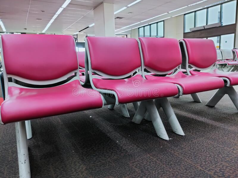 Pink artificial leather chairs lined up waiting to receive passengers in the airport. royalty free stock photo