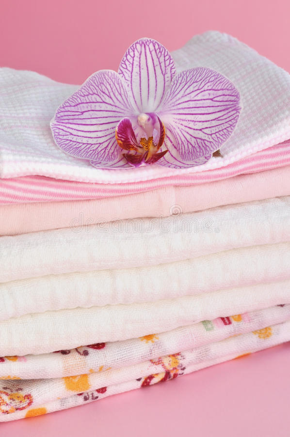 Pink Baby Clothes. Pink orchid on a pile of baby clothes royalty free stock photography