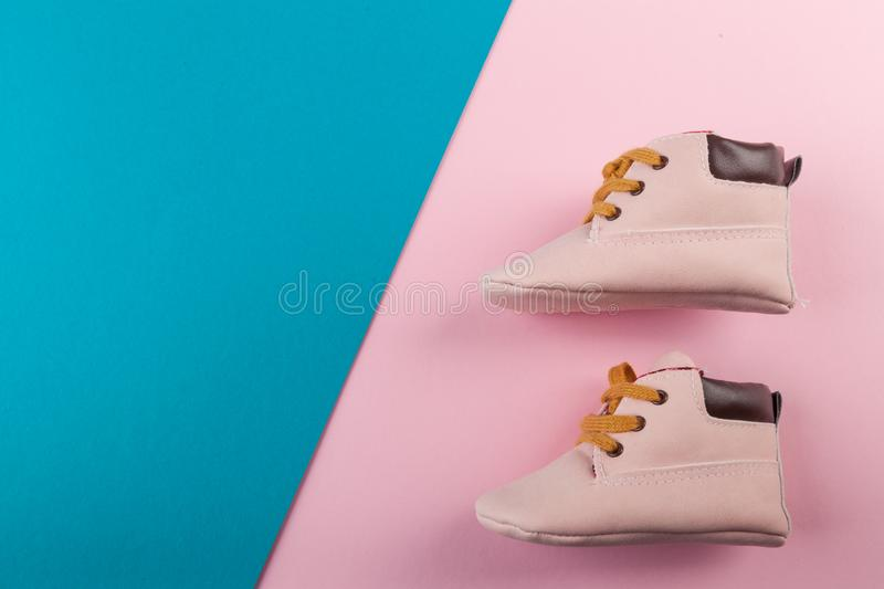 Pink baby shoes on blue and pink background. Fashion for kids background concept stock image