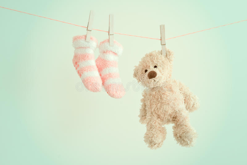 Pink baby socks and teddy bear with copy space. Children background stock photo