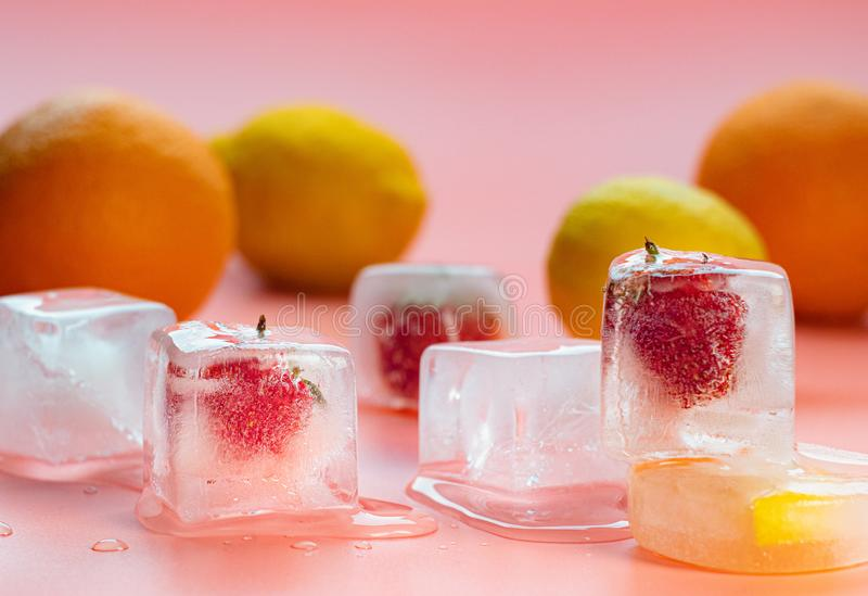 Pink background of fruits on table, close up view. Oranges, yellow lemons and ice cubes on desk. Red strawberries and royalty free stock photo
