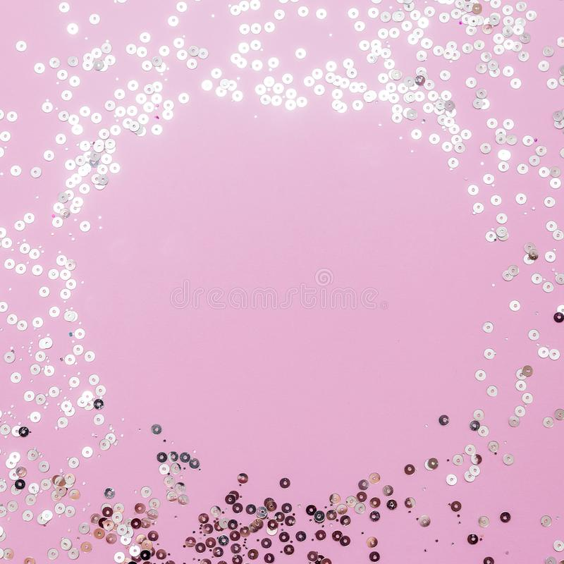 Pink background with holographic sparkles or sequins. Christmas, winter, birthday, celebration flat lay, square cropping. Social stock photography