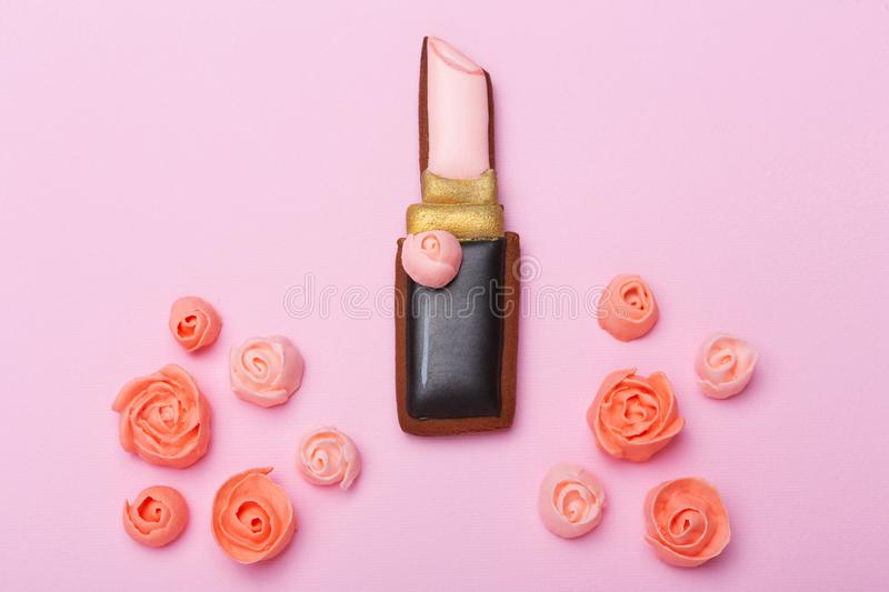 On a pink background lies a gingerbread in the shape of a lipstick, surrounded by sweet flowers, the concept of a holiday royalty free stock images