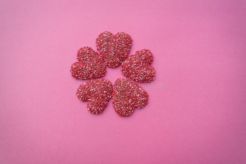 Chocolate hearts. Pink background with red chocolate hearts stock photo