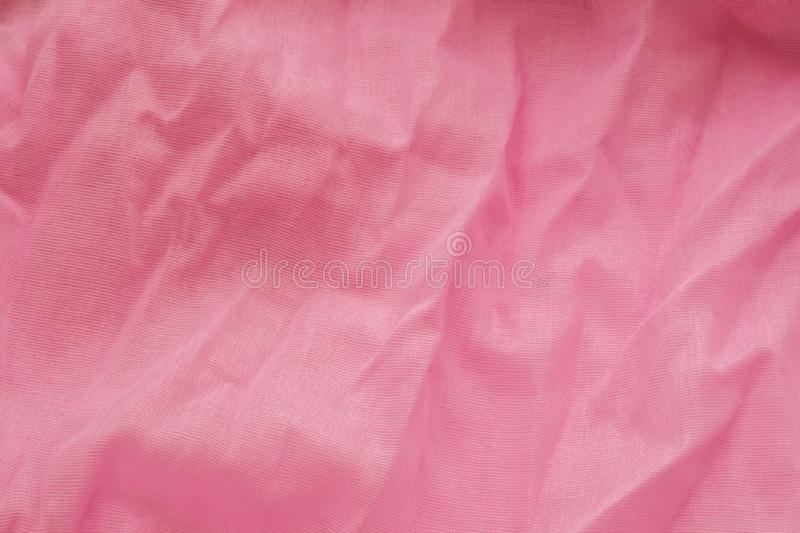Pink background from a textile material with wicker pattern, closeup. Cloth backdrop. Crumpled fabric. Selective focus.  stock photography