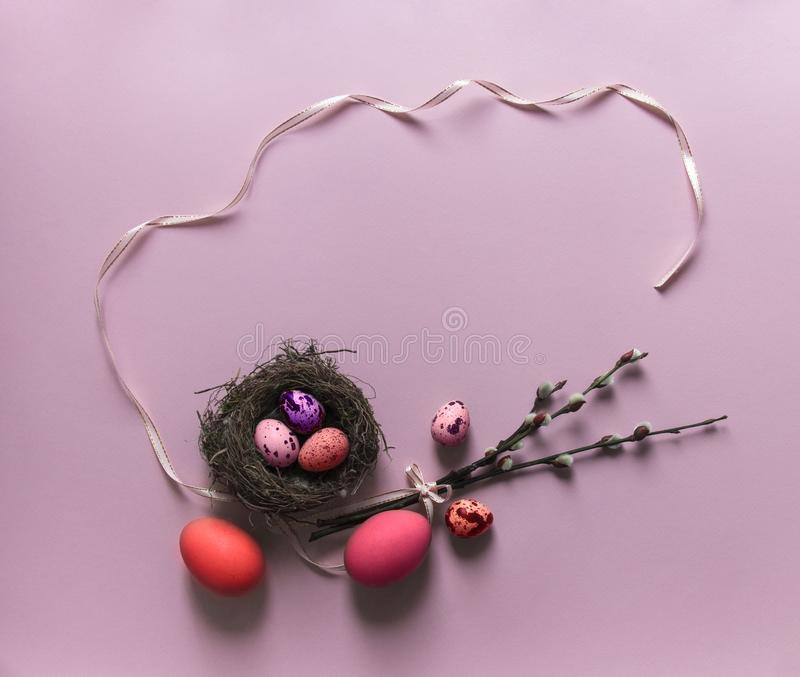 Pink background willow branches blossomed eggs quail chicken nest with three red purple color view from above ribbon bow pink oval royalty free stock photography