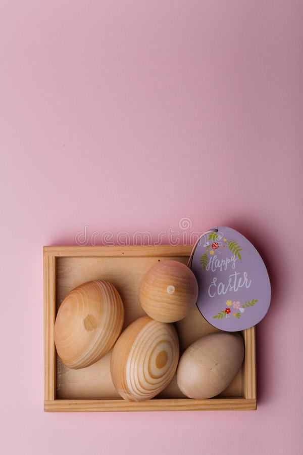On a pink background is a wooden stand in which are wooden eggs, blanks, Easter eggs and a purple card with the inscription happy royalty free stock photography