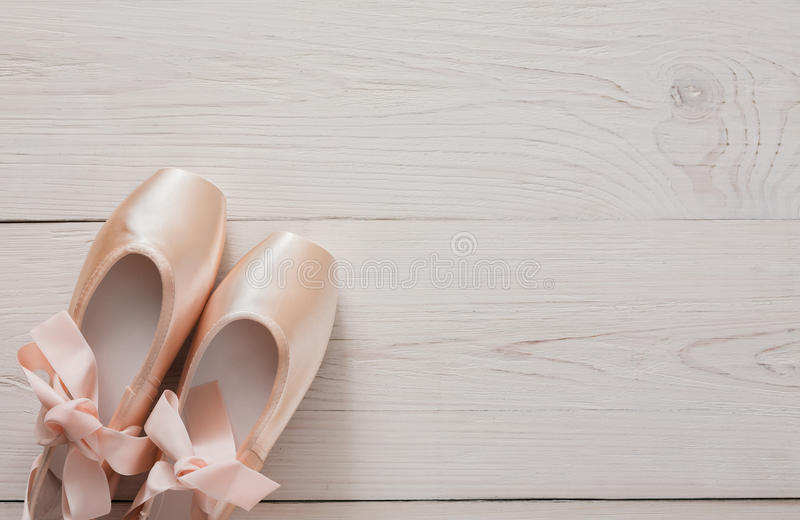 Pink ballet pointe shoes on white wood background royalty free stock images