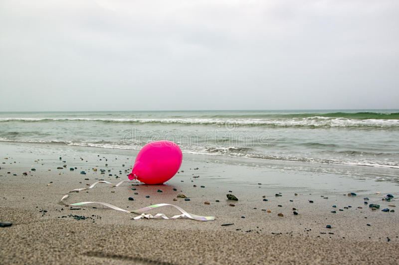 Pink balloon. Abandoned balloon with white ribbon lies on the North Sea beach royalty free stock photos