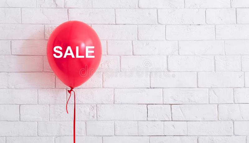 Pink balloon with white text hang out in front of white bricks wall stock photography