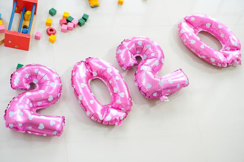 Pink balloons put on the floor together near various type of toys with the text mean to year 2020 or two thousand and twenty royalty free stock photography