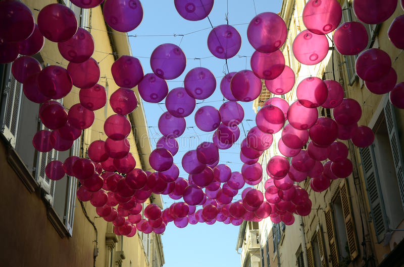 Pink balloons top of a provencal street, in France. Pink balloons top of a provencal street, on blue sky, in France stock photography