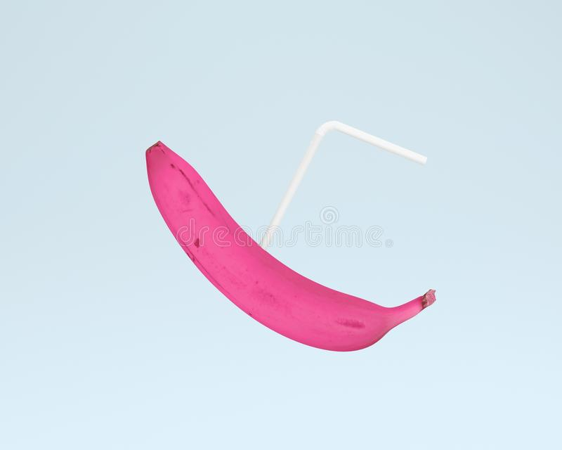 Pink banana with straws on blue color pastel background. minimal stock photo