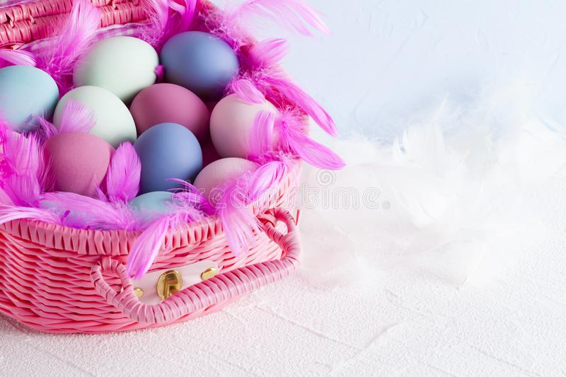 Pink basket full of colored Easter eggs and feathers stock photos