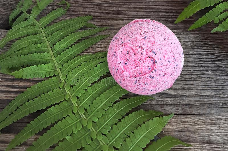Pink bath ball with fern leaf on wooden background. royalty free stock image