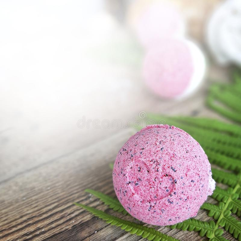 Pink bath ball with fern leaf on wooden background. royalty free stock images