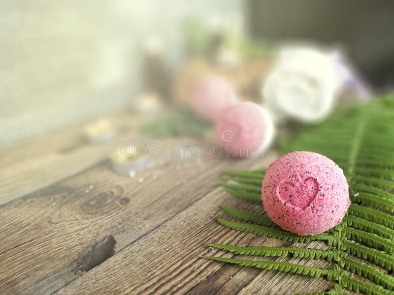 Pink bath bomb with fern leaf  on wooden background. stock photos