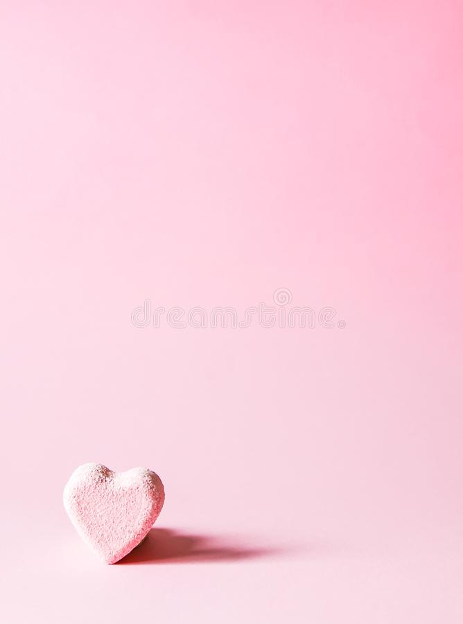 Pink bath bomb in the shape of heart on soft pastel background stock photo
