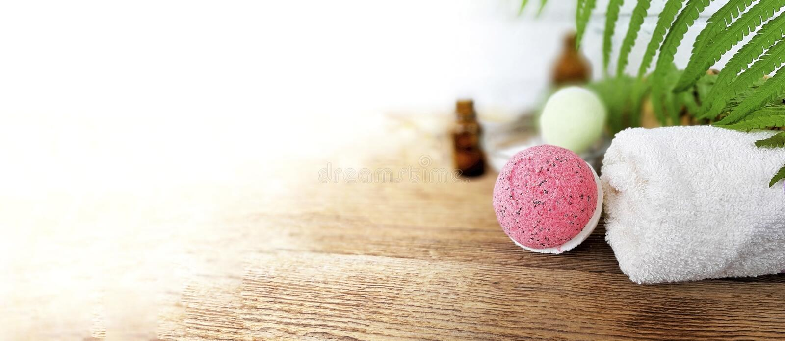 Pink bath bomb with towel  on wooden background. Summer spa aromatherapy concept for vacation and relax.  Banner with copy space, care, body, beauty, treatment royalty free stock photography