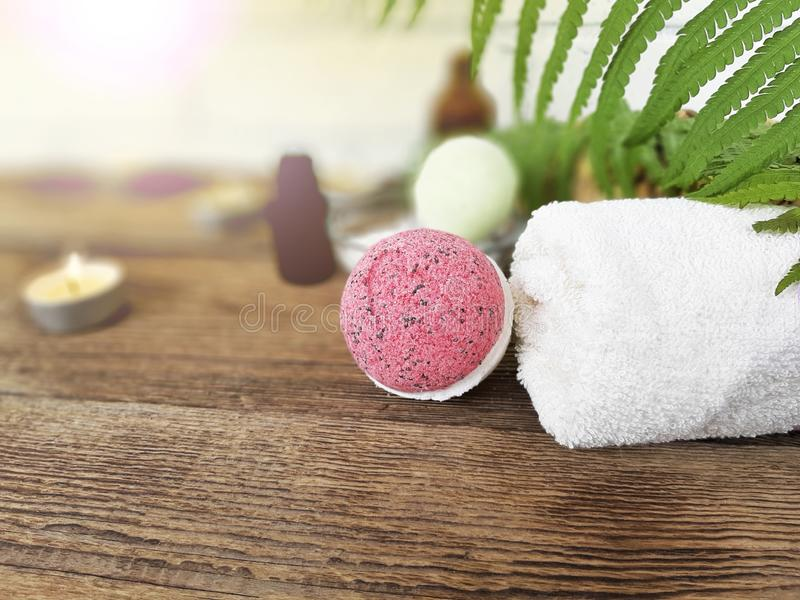 Pink bath bomb with towel  on wooden background. Summer spa life style concept for vacation and relax. Selective focus.  Copy space, care, aromatherapy, body royalty free stock image