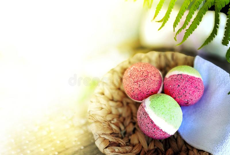 Pink bath bombs in basket with fern leaves  on wooden background. stock photos