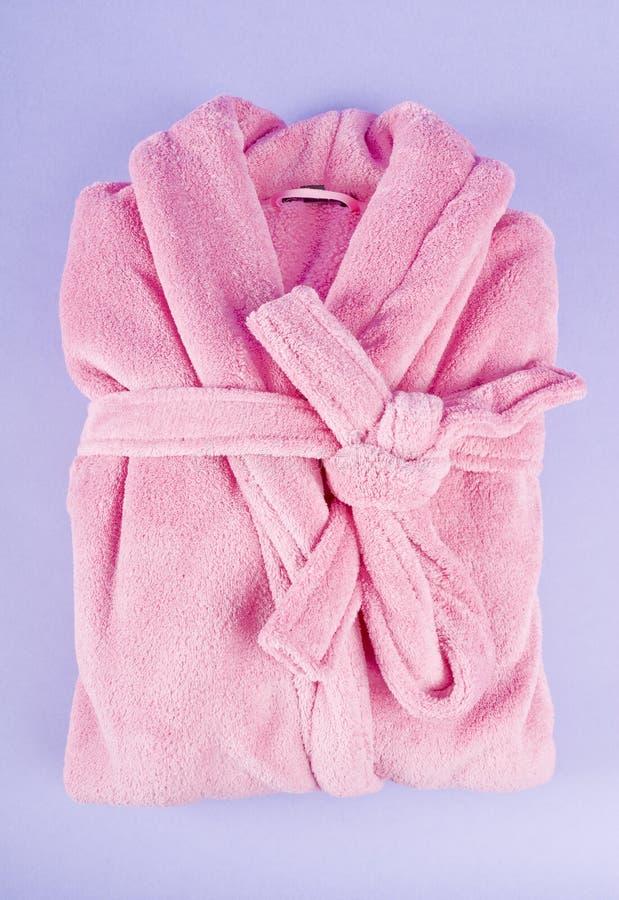 Pink Bathrobe. Soft pink lady's bathrobe on purple background stock photography