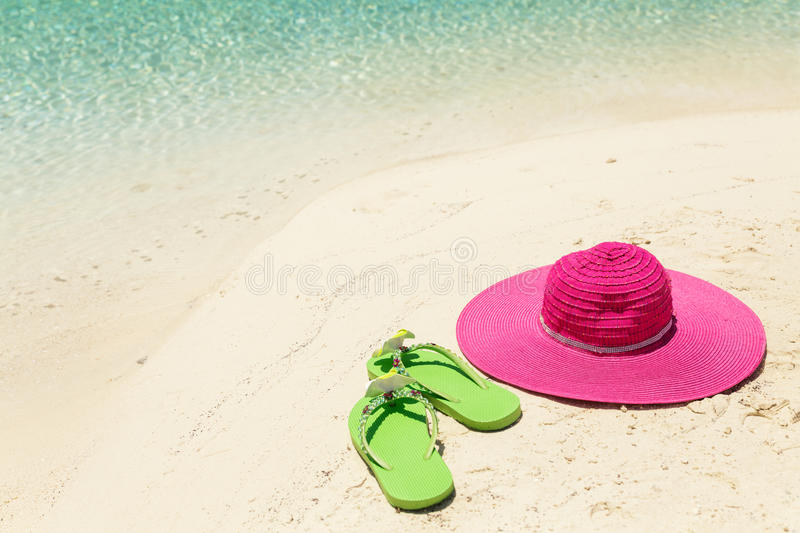Pink beach hat and green slippers in the golden sand by sea shore royalty free stock image