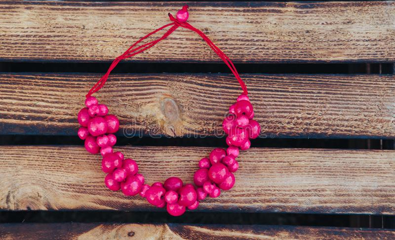 Pink beads handmade. Wooden background. Handmade wood. Top view royalty free stock photos