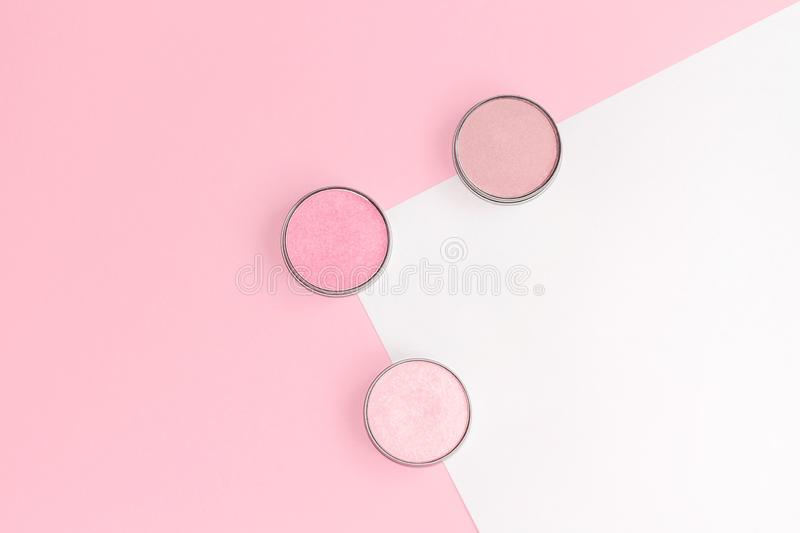 Pink, beige and ivory blushes, eyeshadows or highlighters on pink and white background. Flat lay. royalty free stock image