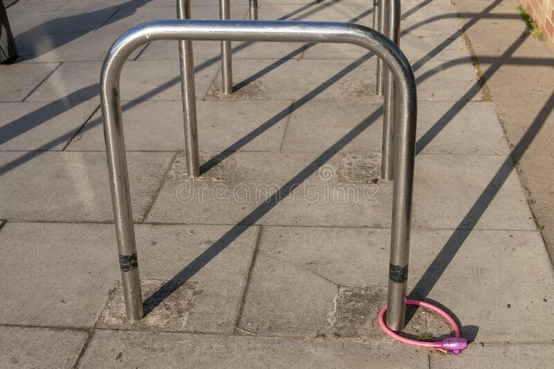 A pink bike lock. A close up view of a pink bike lock and chain connected to a metal bike post royalty free stock photo