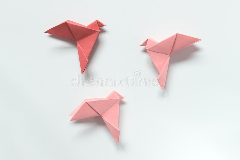 Pink Birds of different shades. Origami. The concept of freedom, inspiration. Pink Birds of different shades. Origami on light background. The concept of stock photo