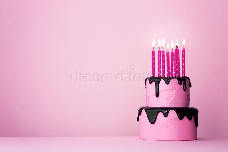 Pink birthday cake with candles stock images