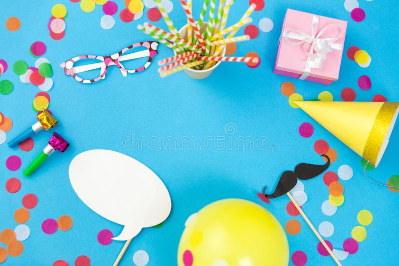 Pink birthday gift and party props. Celebration and decoration concept - pink birthday gift, party props, balloons and colorful confetti on blue background royalty free stock photography