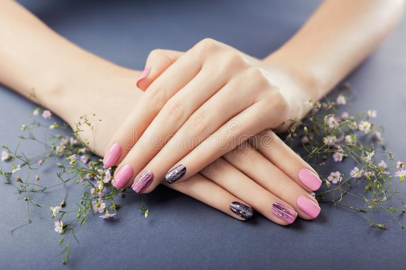 Pink and black manicure with flowers on grey background. Nail art stock photo