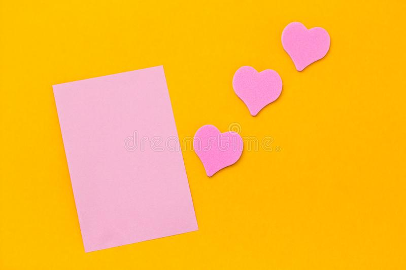pink paper sheet and pink hearts on a yellow background copy space stock photos